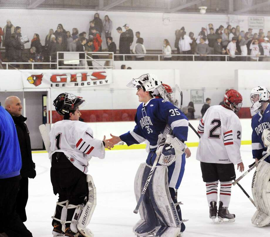 After the boys high school ice hockey game between Greenwich and Darien ended in a 3-3 tie, goaltenders Bryan Archino of Greenwich, left, and Will Massie of Darien, center, shake hands at Hamill Rink in Greenwich, Conn., Tuesday, Feb. 3, 2015. At right is Kevin Piotrzkowski (#2) of Greenwich. Photo: Bob Luckey / Greenwich Time