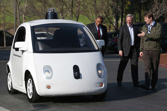 U.S. Trans port ation Secretary Anthony Foxx (left) gets shown a self-driv ing car by Google's Chairman Eric Schmidt and Chris Urmson in February.