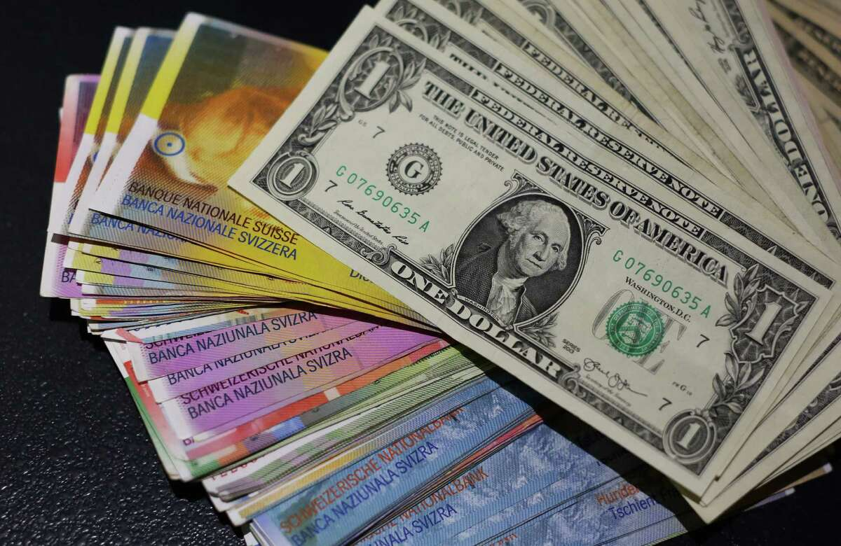 Multiple denomination U.S. dollar bills sit on top of Swiss franc bank notes in this arranged photograph inside a currency exchange store in London, U.K., on Friday, Jan. 16, 2015. Banks and currency traders are tallying the fallout after the Swiss National Bank's unexpected decision to jettison its cap on the franc sent the currency up as much as 41 percent against the euro. Photographer: Chris Ratcliffe/Bloomberg