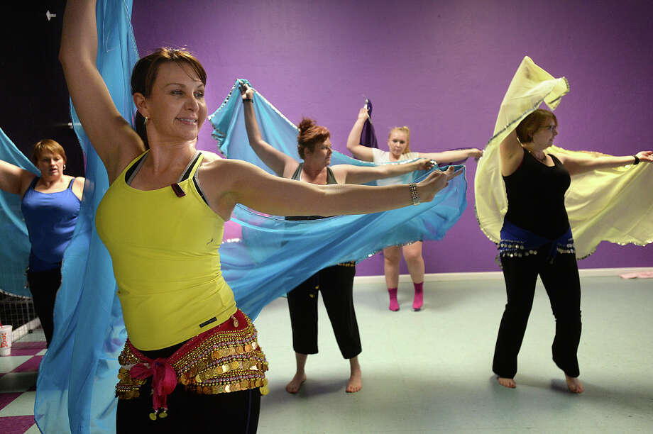 Michele Harrington leads students in her belly dancing class at the Belly Dance Studio in Beaumont Monday. Harrington fell in love with the art form 14 years ago and has immersed herself in both the dance and culture. It has become a passion she shares now with her students, many of whom seek the healthy benefits of the Middle Eastern dance.  Photo taken Monday, February 2, 2015  Kim Brent/The Enterprise Photo: Kim Brent / Beaumont Enterprise