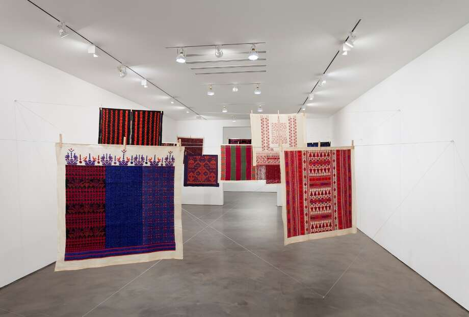 """Twelve Windows,"" an installation by Mona Hatoum with Inaash, is on view through Feb. 8 at the Museum of Fine Arts, Houston. 9 2012-2013, 12 pieces of Palestinian embroidery on fabric, wooden clothes pegs, steel cable, each embroidery: 39 3/8 x 39 3/8 inches (100 x 100 cm.) Installation view at Alexander and Bonin Gallery, New York,  Mona Hatoum, 2014; photograph  Joerg Lohse. 2012-2013, 12 pieces of Palestinian embroidery on fabric, wooden clothes pegs, steel cable, each embroidery: 39 3/8 x 39 3/8 inches (100 x 100 cm.) Installation view at Alexander and Bonin Gallery, New York,  Mona Hatoum, 2014; photograph  Joerg Lohse.) Photo: Joerg Lohse"