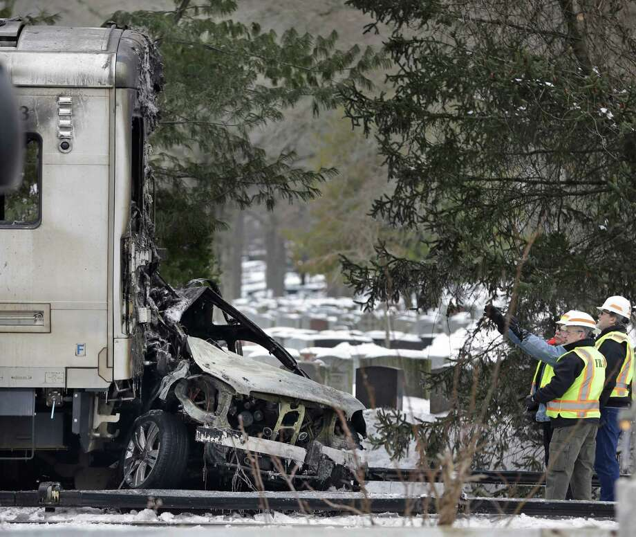 Authorities wearing Federal Railroad Administration vests look over the wreckage of a Metro-North Railroad train and a SUV in Valhalla, N.Y., Wednesday, Feb. 4, 2015.  Five train passengers and the SUVâÄôs driver were killed in Tuesday eveningâÄôs crash in Valhalla, about 20 miles north of New York City. Authorities said the impact was so forceful the electrified third rail came up and pierced the train. Photo: Seth Wenig, Associated Press / Associated Press AP Photo/Seth Wenig