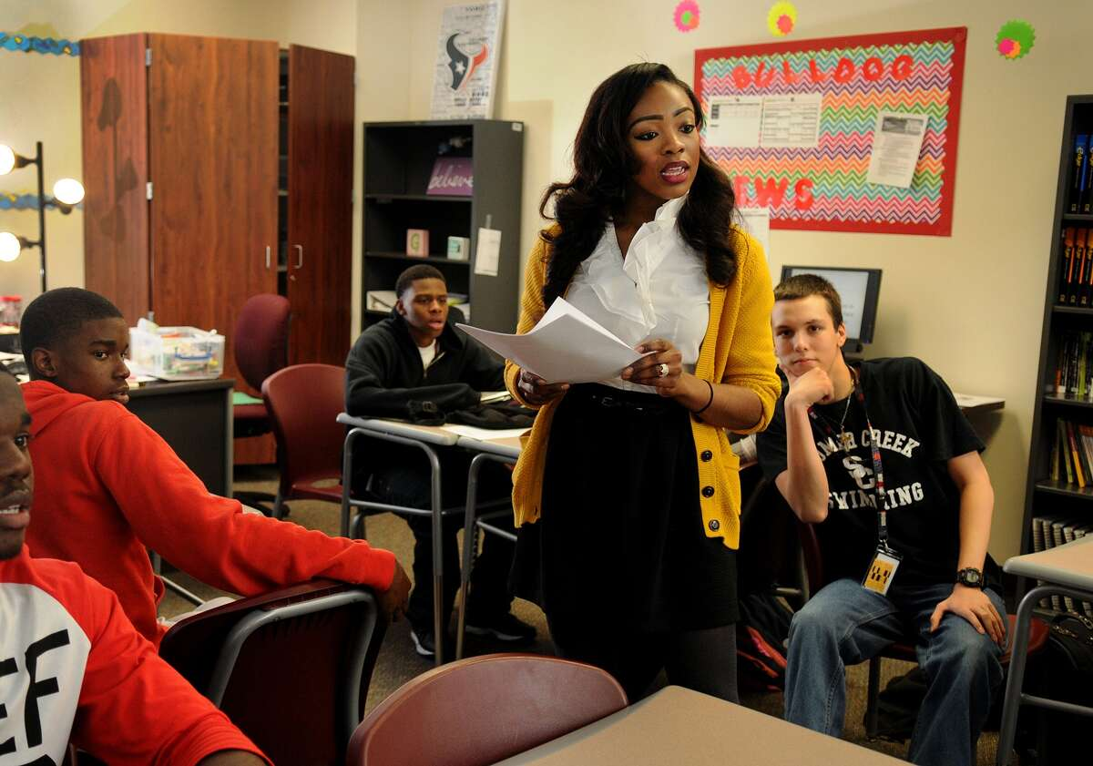 Houston Texans cheerleader Elizabeth Gardner, center, teaches her practical writing class, with seniors Jahmarley Brannigan, left, X-Zavion Wilson and Caleb Del Real at Summer Creek High School. Gardner became a cheerleader and a teacher in 2014. She hopes to try out again for the team in March.