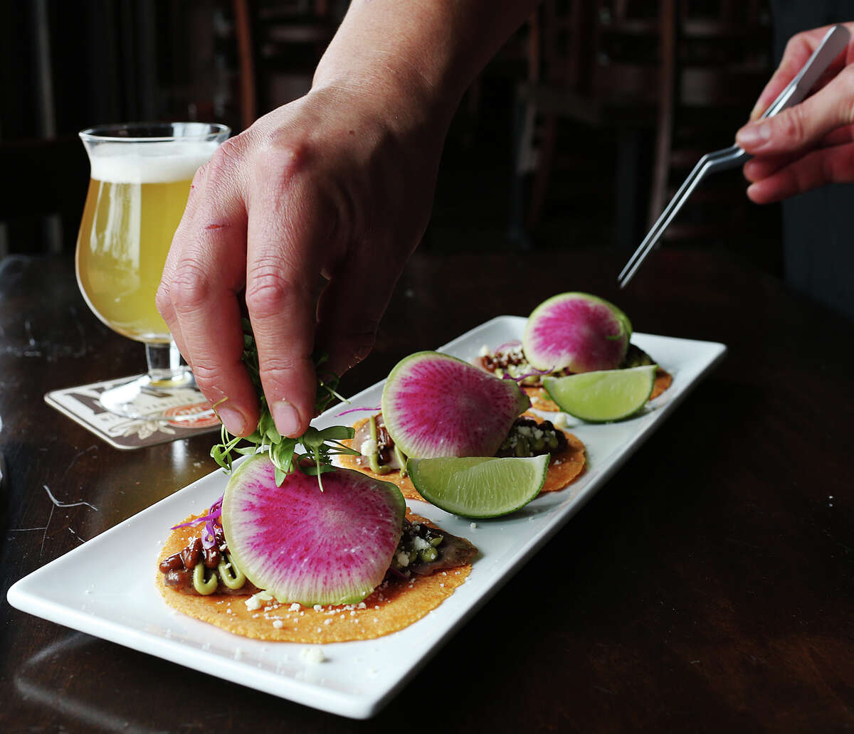 The duck breast carnitas tacos are served on Gochujang tortillas topped with avocado puree, salsa roja, red cabbage, watermelon radish, cotija cheese and micro cilantro at The Hoppy Monk, Tuesday, Feb. 3, 2015. The establishment is located off Loop 1604 in the Stone Oak area.
