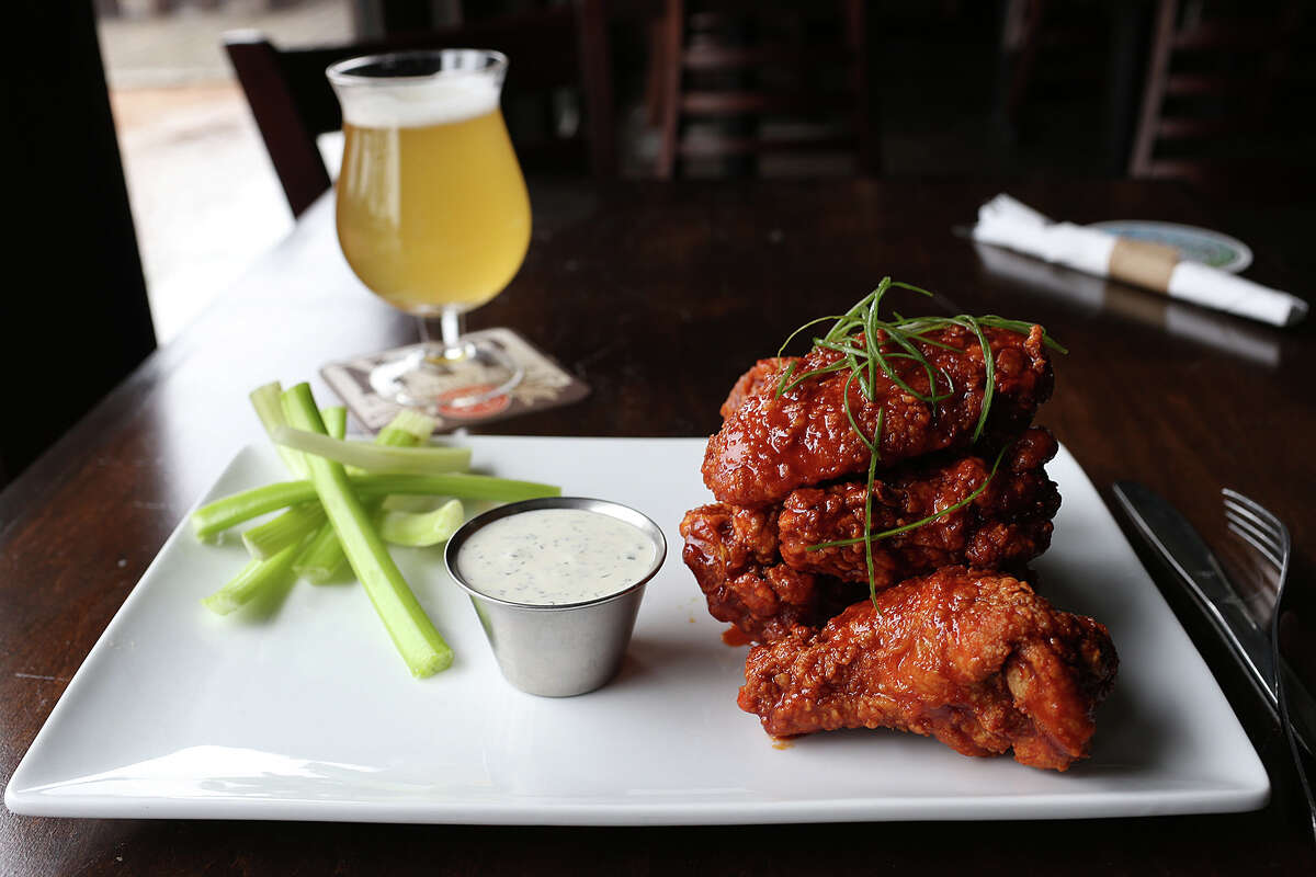 The Korean fried chicken wings are served with celery sticks and house-made ranch dressing at The Hoppy Monk. The establishment is located off Loop 1604 in the Stone Oak area.