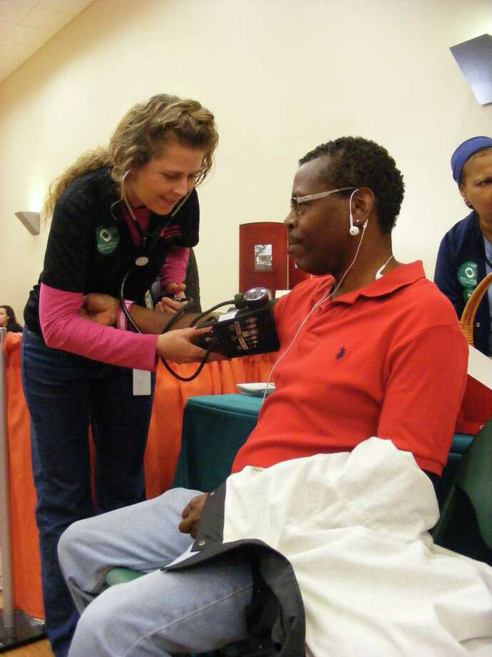 Kathy Voigt, a nurse with WellMed in Schertz, checks the blood pressure of Serge Valbrun Saturday, Jan. 31, at the Health and Wholeness Fair in the Schertz Civic Center. The fair, co-sponsored by Baptist Emergency Hospital and the Schertz Chamber of Commerce, drew 559 attendees. Photo: /David DeKunder / Northeast Herald
