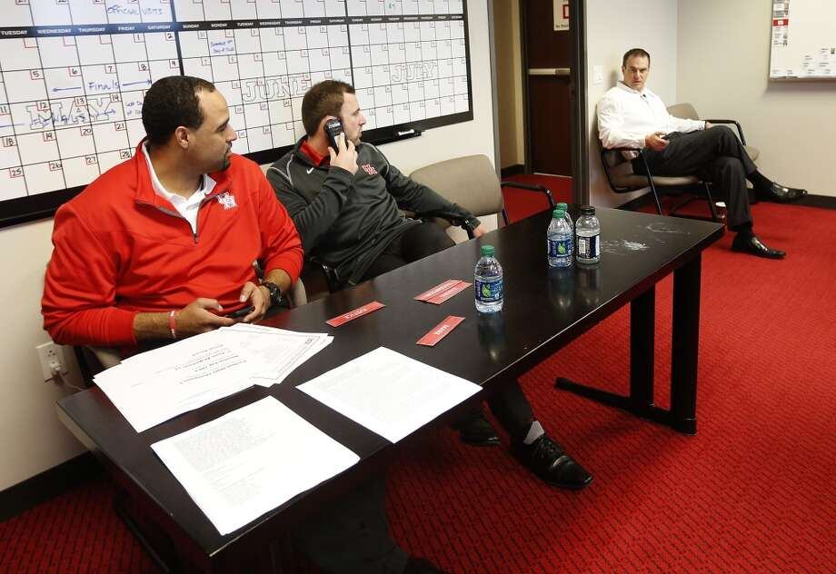 University of Houston head football coach Tom Herman chats with Adrian Mayes, Director for Recruiting, and Drew Mehringer, wide receivers coach, as Herman signed his first class in the war room at UH, Wednesday, Feb. 4, 2015, in Houston.  ( Karen Warren / Houston Chronicle  ) Photo: Karen Warren, Houston Chronicle