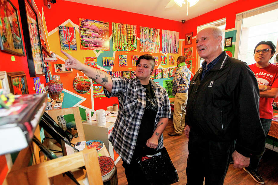 Nina Donley (left) shows some of her work to County Commissioner Tommy Adkisson during the grand opening of her art gallery, Zac Cimi Arte, at the Gardens at San Juan Square, 2003 S. Zarzamora #3104, on Saturday, Dec. 20, 2014.  Donley currently is showcasing work from 16 local artists as well as her own at her gallery.  MARVIN PFEIFFER/ mpfeiffer@express-news.net Photo: Marvin Pfeiffer, Staff / San Antonio Express-News / Express-News 2014