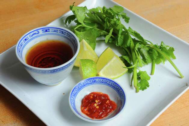 Tai food staple ingredient fish sauce, cilantro, lime and chili garlic sauce on Tuesday Jan. 27, 2015 in Delmar , N.Y. (Michael P. Farrell/Times Union) Photo: Michael P. Farrell / 00030183A