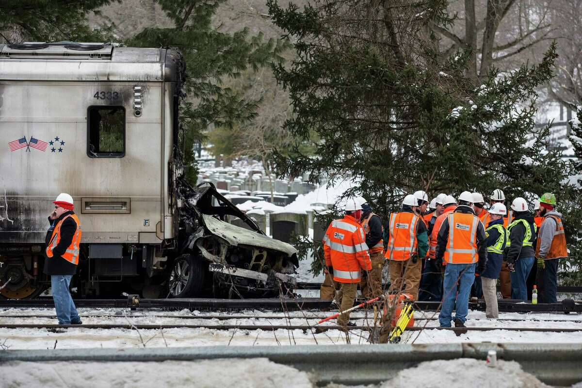 Officials inspect a Metro-North train crash with a sport utility vehicle that occured last night on February 4, 2015 in Valhalla, New York. The crash started a fire in the train cars that killed seven people, including the driver of the vehicle.
