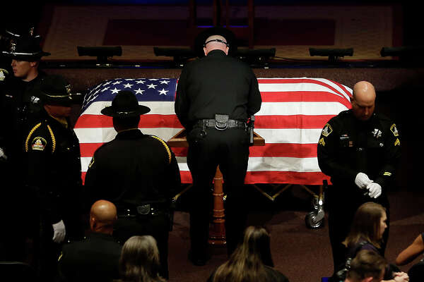 A Sacramento County Sheriff's Deputy stands over the flag-draped coffin of  slain Sacramento County Deputy Danny Oliver, after a memorial service in Roseville, Calif. Monday, Nov. 3, 2014.  Oliver and Placer County Sheriff's Detective Michael Davis Jr. were shot and killed in a shooting spree that spanned two Northern California counties, Oct. 26.   Luis Enrique Monroy-Bracamonte, who was booked into the Sacramento County jail under the pseudonym Marcelo Marquez, faces murder charges in the killing of the two deputies, and the wounding of another deputy and a bystander.