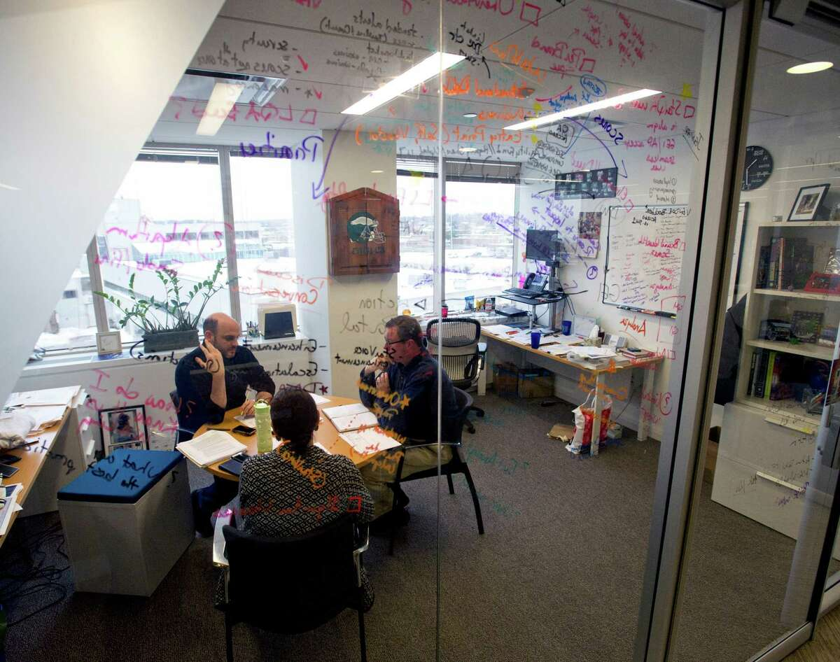 Starwood Hotels employees meet in Matt Valenti's office where the glass walls, which help fill the interior of the office space with natural light, also serve as a white board on Tuesday, February 4, 2015. The office building is the only LEED Platinum building in Farifield County.