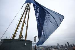 Washington State Governor Jay Inslee staff member Jaime Smith tries to unfurl a flag raised by the Governor and Seattle Mayor Ed Murray in light wind on the top of the Space Needle on Wednesday, February 4, 2015. The flag thanks the Seattle Seahawks for the 2014 season. (Joshua Trujillo, seattlepi.com)