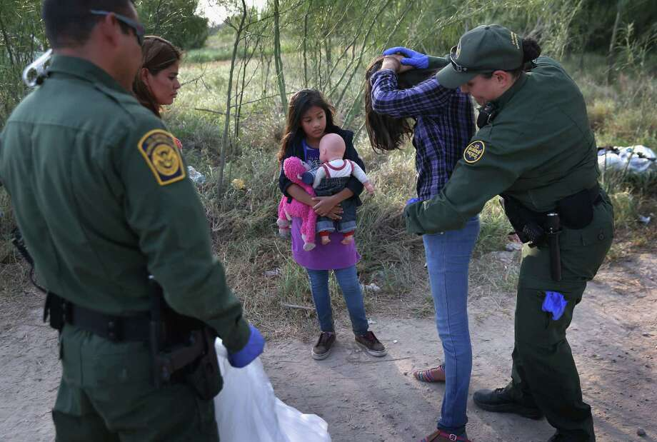 Border Patrol agents search a Salvadoran girl as her sister watches after the two were caught crossing the border illegally at Mission, Texas, in July.  (Photo by John Moore/Getty Images) Photo: John Moore, Staff / 2014 Getty Images