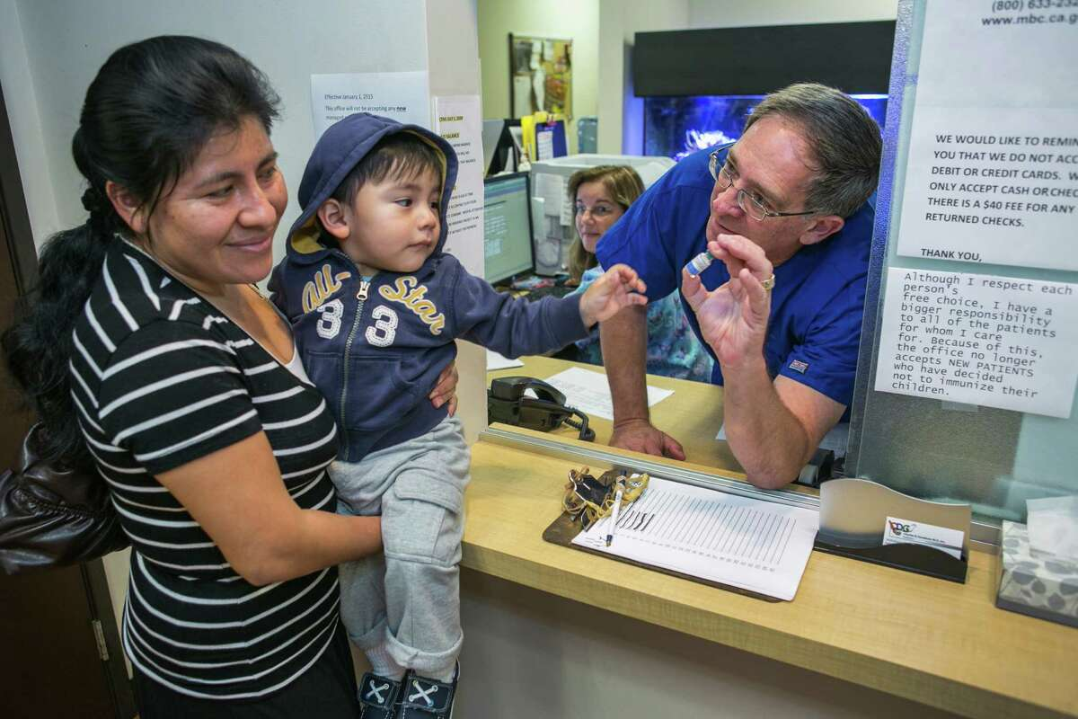 Pediatrician Charles Goodman, talks with patient Carmen Lopez, 37, holding her 18-month-old son, Daniel after being vaccinated with the measles-mumps-rubella vaccine, or MMR at his practice in Northridge, Calif., Thursday, Jan. 29, 2015. Some doctors are adamant about not accepting patients who don't believe in vaccinations, with some saying they don't want to be responsible for someone's death from an illness that was preventable. Others warn that refusing treatment to such people will just send them into the arms of quacks. (AP Photo/Damian Dovarganes)