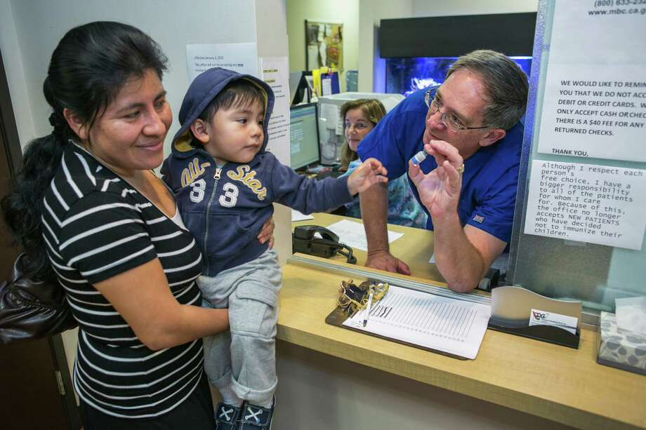 Pediatrician Charles Goodman, talks with patient Carmen Lopez, 37, holding her 18-month-old son, Daniel after being vaccinated with the measles-mumps-rubella vaccine, or MMR at his practice in Northridge, Calif., Thursday, Jan. 29, 2015. Some doctors are adamant about not accepting patients who don't believe in vaccinations, with some saying they don't want to be responsible for someone's death from an illness that was preventable. Others warn that refusing treatment to such people will just send them into the arms of quacks. (AP Photo/Damian Dovarganes) Photo: Damian Dovarganes / Associated Press / AP