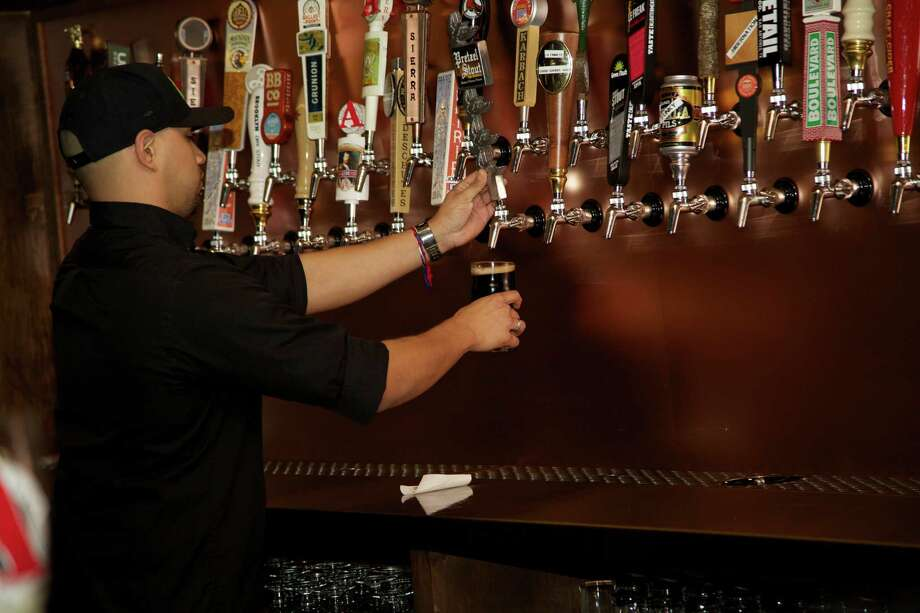 Joshua Sotello is working the bar at the Hoppy Monk. Photo: Xelina Flores / For the Express News