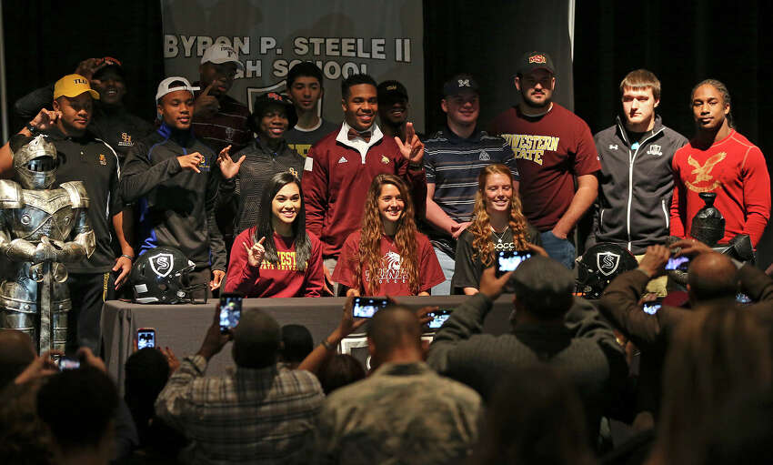 Scholarship athletes pose for a group picture after a signing ceremony in their school's auditorium on February 4, 2015.
