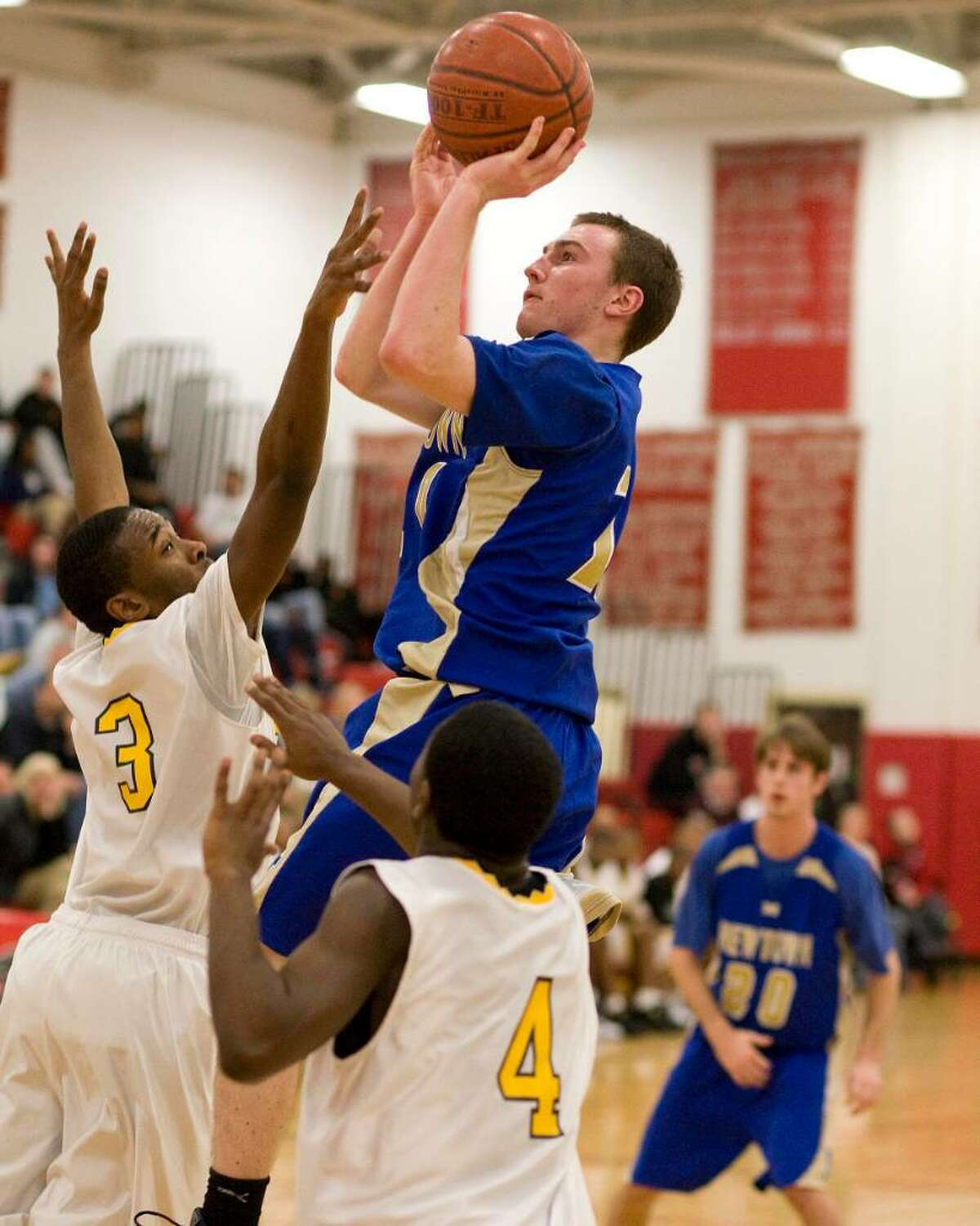 Newtown's Dan Lynch goes up for a shot over Kolbe Cathedral defender Cosrick McDonald (3) during the Nighthawks' SWC Tournament semifinal victory Tuesday night at Pomperaug High School.