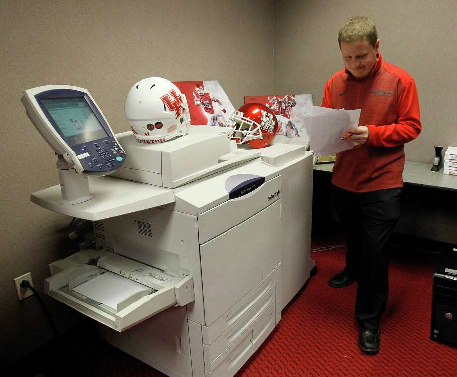 Scotty Harydzak mans one of the University of Houston's three fax machines set up to receive letters of intent on Wednesday. Thirteen of the 17 recruits in Tom Herman's first UH football class opted to fax their letters over emailing them. Photo: Karen Warren, Staff / © 2015 Houston Chronicle