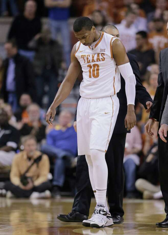 Texas' Jonathan Holmes (10) is helped off the court after he was injured during the second half of an NCAA college basketball game against Oklahoma State, Wednesday, Feb. 4, 2015, in Austin, Texas. Oklahoma State won in overtime 65-63. (AP Photo/Eric Gay) Photo: Eric Gay, STF / Associated Press / AP