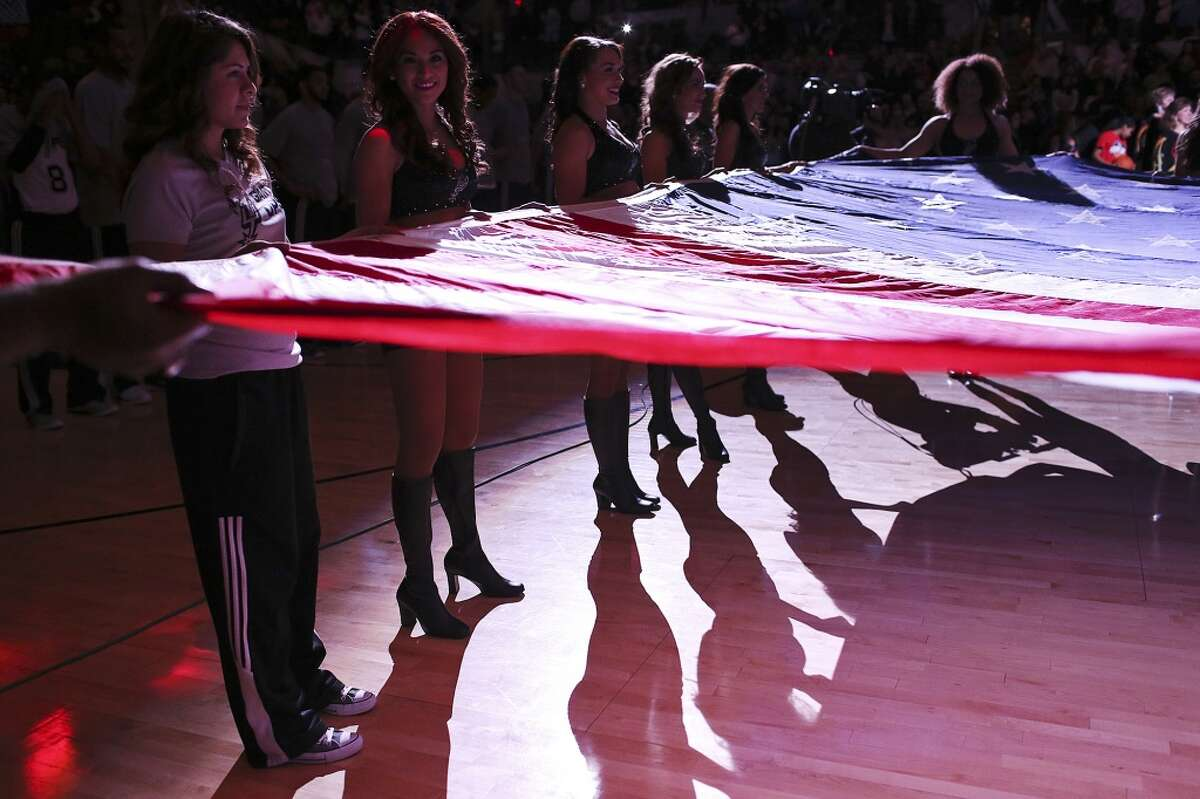 The San Antonio Silver Dancers hold up a U.S. flag before the start of the San Antonio Spurs and Orlando Magic game at the AT&T Center, Wednesday, February 4, 2015.