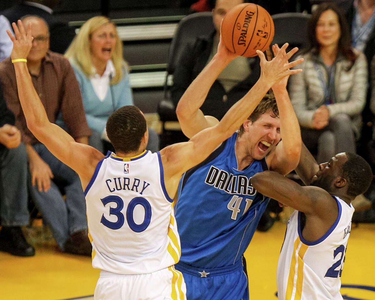 Dallas Mavericks forward Dirk Nowitzki (41) is defended by Golden State Warriors guard Stephen Curry (30) and Golden State Warriors forward Draymond Green (23) during the third quarter of an NBA game, Wednesday, Feb. 4, 2015, at the Oracle Arena in Oakland, Calif.