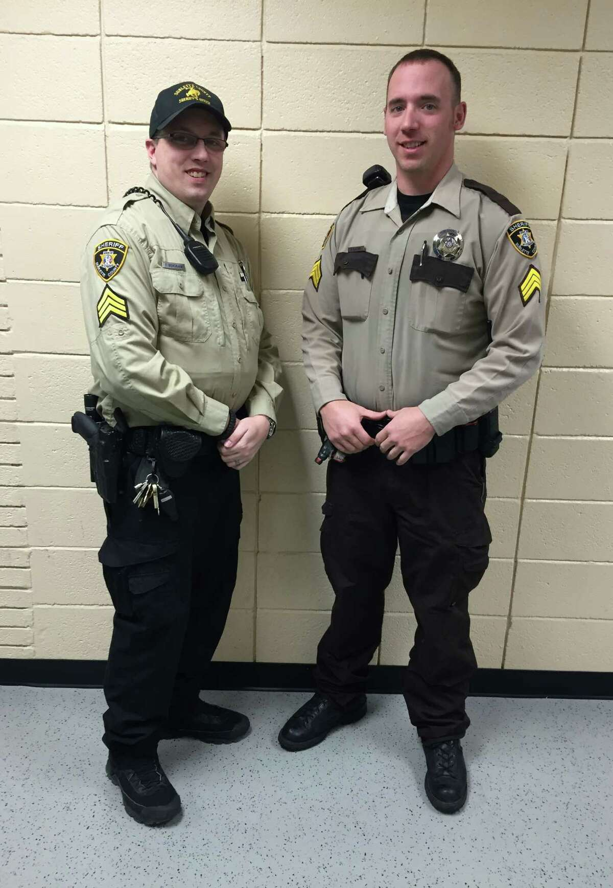 In this photo provided by the Sublette County Sheriff's Office, Detention Sergeant Travis Bingham, left and Patrol Sergeant Rich Kaumo pose in two of the different uniforms previously utilized by the Sublette County Sheriff at the Sheriff's Office on Monday, Feb. 2, 2015, in Pinedale, Wyo. The new sheriff of a Wyoming county has banned his deputies from wearing cowboy hats and cowboy boots, a change that led one longtime deputy to retire rather than give up his Western attire. Sublette County Sheriff Stephen Haskell imposed the new dress code in the western Wyoming county that includes Pinedale, which True West magazine recently named a true Western town.