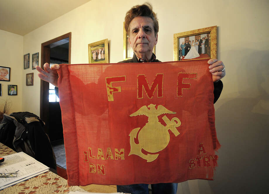 Vietnam veteran John Rey holds the unit flag from Alpha Battery 1st Light Anti-aircraft Missile Battalion, the first combat group to land in Vietnam, at his home in Norwalk, Conn. on Wednesday, February 4, 2015. Photo: Brian A. Pounds / Connecticut Post