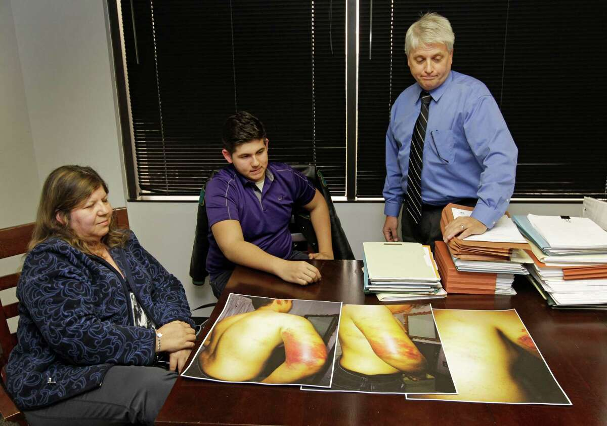 Guadalupe Suquet, left, and her son, Cesar Suquet, talk with attorney Mark Montgomery , right, Thursday, Jan. 15, 2015, in Houston about the photos showing Cesar's injuries from being beaten by a Pasadena ISD Police Officer. The officer used a nightstick to strike Cesar 18 times on the neck, back and arm.