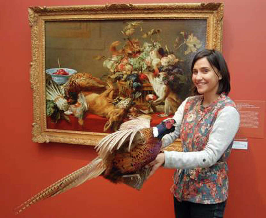 Tara Contractor holds a Ring-necked Pheasant, one of the animals that families can search for among the paintings featured in the Bruce Museum's ARTventure program on February 22. Photo: Photo By Cynthia Ehlinger /Bruce, Contributed Photo / Greenwich Time Contributed