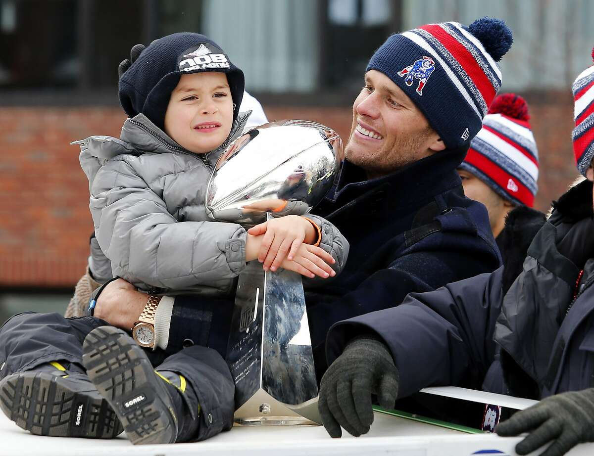 NOT TOO HARD, SON. DON'T WANT TO DEFLATE IT: Tom Brady's son, Benjamin, hugs the Vince Lombardi Trophy during a Super Bowl victory parade in Boston.