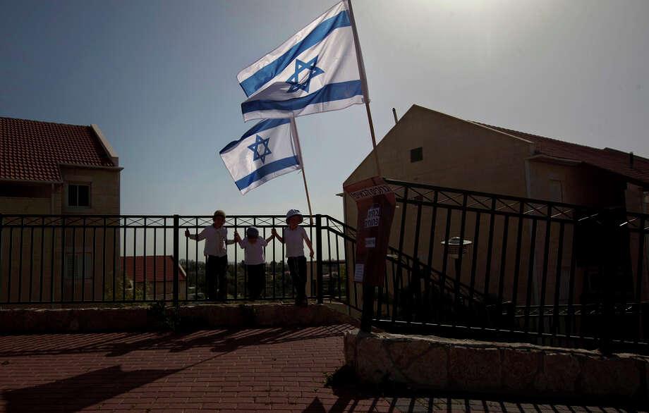 Israeli flags fly over the Ulpana neighborhood in the West Bank settlement of Beit El near Ramallah. Photo: Sebastian Scheiner / Associated Press / AP