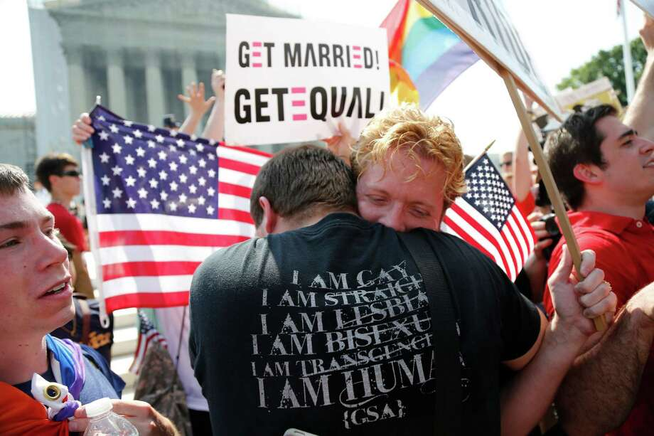 Michael Knaapen (left) and his husband, John Becker, embrace outside the U.S. Supreme Court in Washington after the court struck down a federal provision in 2013 denying benefits to legally married gay couples. Americans narrowly favor allowing same-sex couples in their states to legally marry, a new Associated Press-GfK poll finds. But that support comes with caveats, and there is a close division in the country over the upcoming Supreme Court case that could make same-sex marriage legal nationwide. Photo: Charles Dharapak / Associated Press / AP