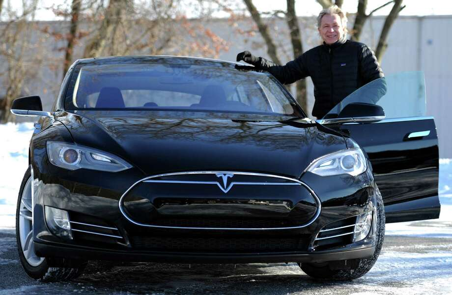 Roger Van Brussel, a Milford resident and business owner, stands in front of his new Tesla Model S 85 Thursday, Feb. 5, 2015, in Milford, Conn. Van Brussel had to leave the state to purchase the electric car but Connecticut is contemplating changing its laws so that Tesla can sell its cars here. Currently, only franchised car dealerships can sell cars in this state, not manufacturers. Photo: Autumn Driscoll / Connecticut Post