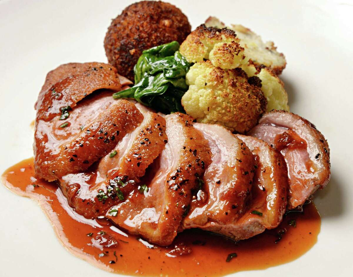 Maple Leaf Farms duck, Arancini, roasted cauliflower and sour cherry demi glaze at Mio Posto restaurant at 68 Putnam Street Tuesday Jan. 27, 2015, in Saratoga Springs, NY. (John Carl D'Annibale / Times Union)