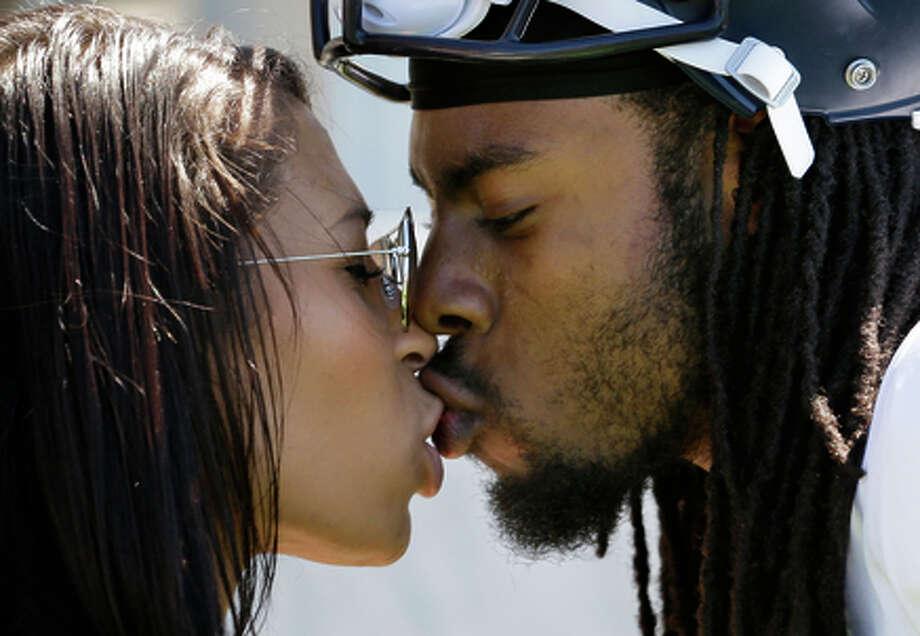 Richard Sherman, right, kisses his girlfriend, Ashley Moss, following an NFL football camp practice in Renton, Wash. Photo: Elaine Thompson / Associated Press / AP