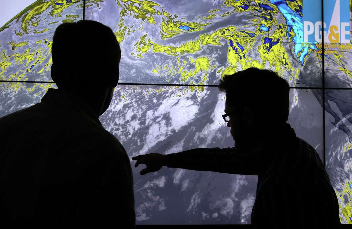 PG&E meteorologists Mike Voss (left) and Scott Strenfel track storm systems forming over the Pacific, as they prepare for one heading toward the Bay Area.