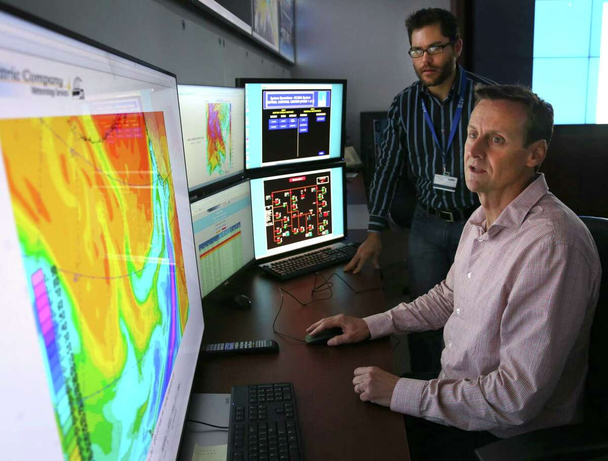 Meteorologists Scott Strenfel (left) and Mike Voss monitor a satellite image depicting an atmospheric river of water vapor approaching the Bay Area at the PG&E Technology Center in San Ramon. PG&E meteorologists use the forecasts to help the utility determine deployment of its repair crews ahead of the storm.