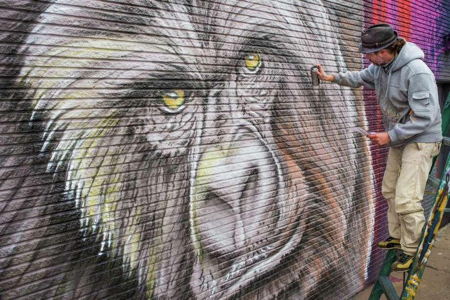 "Sebastien ""Mr. D"" Boileau works on a mural at 2119 Washington in February 2015. The Houston Zoo and business owners sponsored works by five artists to celebrate the zoo's new gorillas. Photo: Brett Coomer, Houston Chronicle / © 2015 Houston Chronicle"
