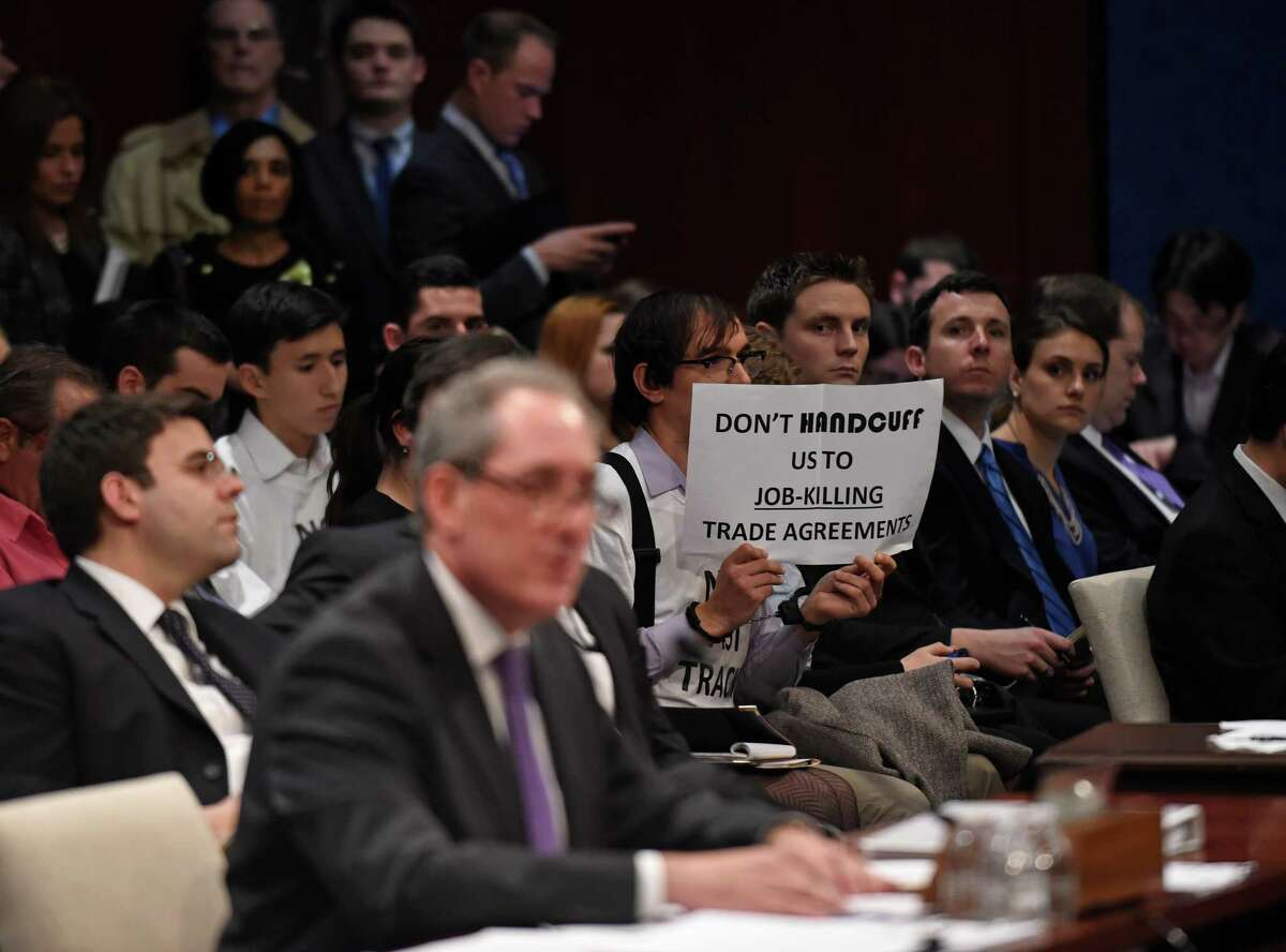 A demonstrator holds up a sign as U.S. Trade Representative Michael Froman testifies on Capitol Hill in Washington, Tuesday, Jan. 27, 2015, before the House Ways and Means Committee hearing on the U.S. trade policy. (AP Photo/Susan Walsh)