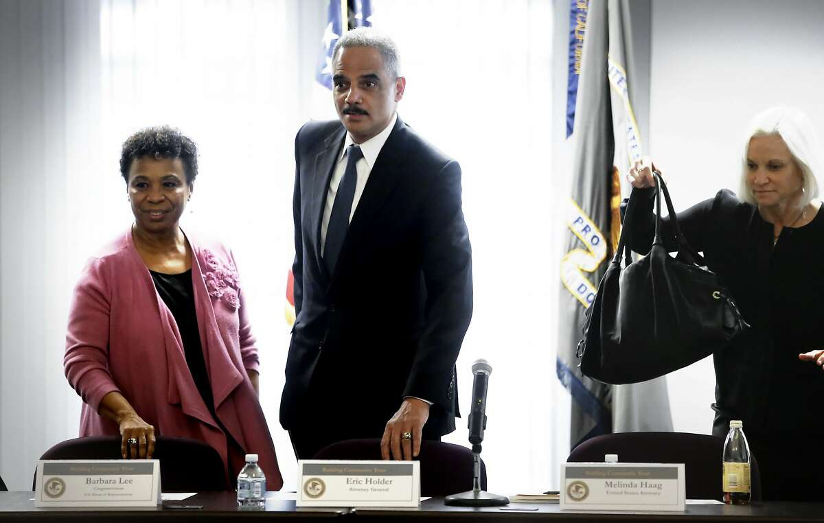 FILE-- U.S. Attorney General Eric Holder is joined by Congresswoman Barbara Lee, (left) and U.S. Attorney Melinda Haag, as they begin a meeting with with local politicians and community leaders for a round table discussion about improving relationships between law enforcement and communities, at the Ron Dellums Federal Building in Oakland on Thursday Feb. 5, 2015. Holder has come out against proposals in Chicago and New Jersey to require fingerprint background checks of drivers for Uber and Lyft.