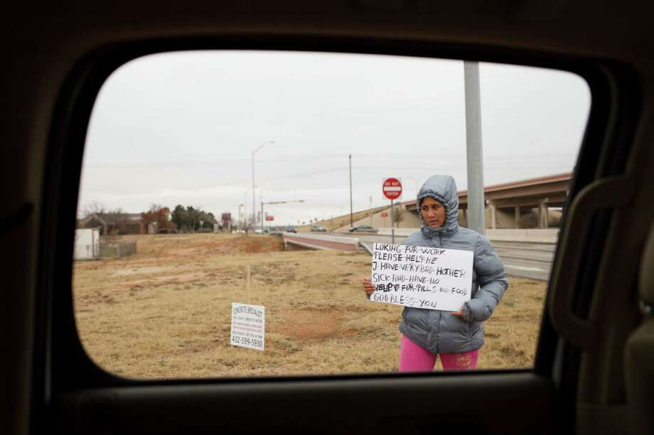 Plunging oil prices could spell economic distress in some quarters. A women begs on the side of the road in Midland, Texas, Jan. 14, 2015. With oil prices plummeting by more than 50 percent since June, the gleeful mood of recent years has turned glum here in West Texas as the frenzy of shale oil drilling has come to a screeching halt. Photo: MICHAEL STRAVATO /New York Times / NYTNS