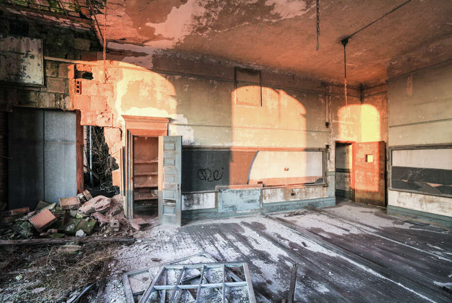 Dawn breaks in a crumbling classroom of P.S. 186 in Harlem.  After forty years of neglect, saplings sprout from the upper floors of the school. Photo: Will Ellis, Courtesy Will Ellis / 2015