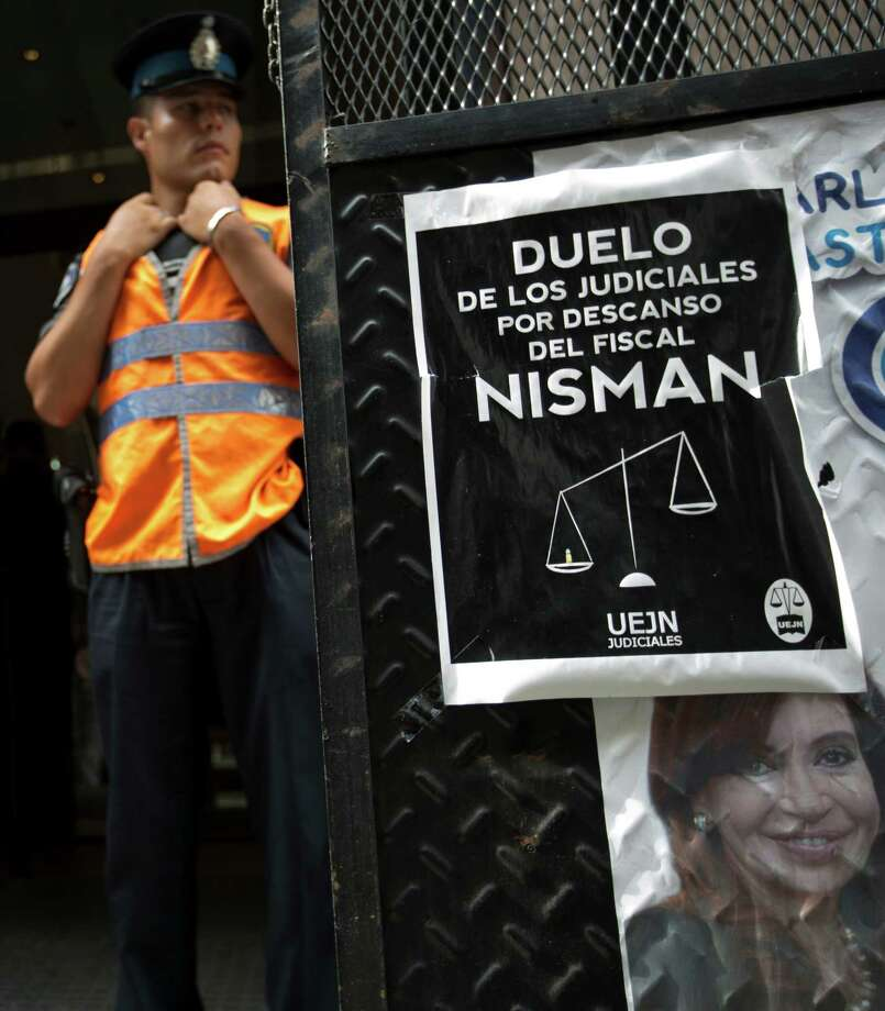 "A police officer stands guard in front of he prosecutor's office that leads the investigation of prosecutor Alberto Nisman's death, in Buenos Aires, Argentina, Thursday, Feb. 5, 2015. Posted on the gate is a portrait of Argentina's President Cristina Fernandez along with another poster that reads in Spanish ""Mourning of judicial workers due to the death of prosecutor Nisman."" Investigators examining the death of Nisman who accused President Fernandez of agreeing to shield the alleged masterminds of a 1994 terror bombing said Tuesday they found a draft document he wrote requesting her arrest. (AP Photo/Rodrigo Abd) Photo: Rodrigo Abd, STF / AP"
