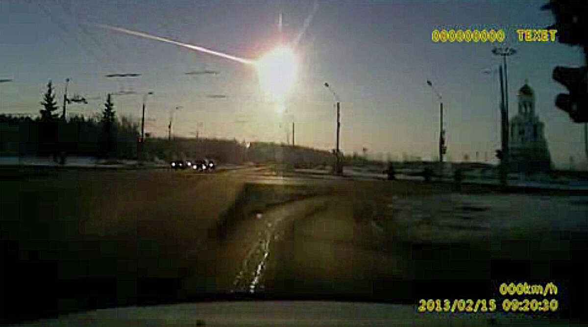 In this image from a dashboard camera video, a meteor streaks across the sky in Russia in 2013.