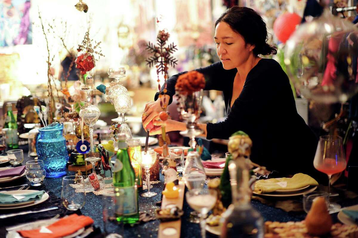 """Cari Borja lights candles along a table set for guests that will be attending her 58th salon dinner party, held at her studio work space in Berkeley on Saturday, January 17, 2015. Borja brings together guests from all those worlds for regular salon dinners with the theme of """"the people we meet, the stories we tell, the meals we remember."""""""