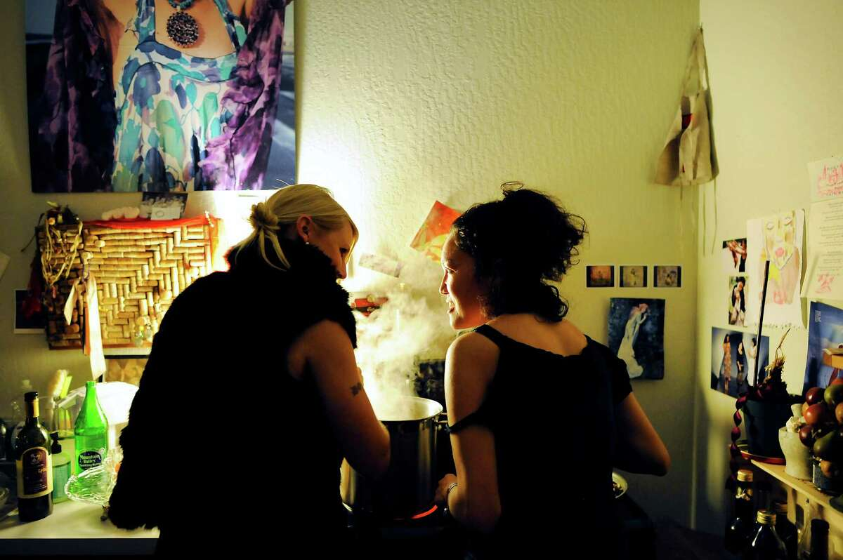 Cari Borja, right, and Eve Love chat over a steaming pot as they work preparing food for guests attending a salon dinner party.