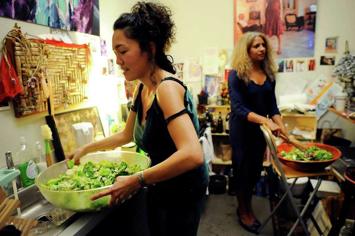 Cari Borja, left, works in the kitchen mixing salads for guests with her friend and helper Jennifer Jones.