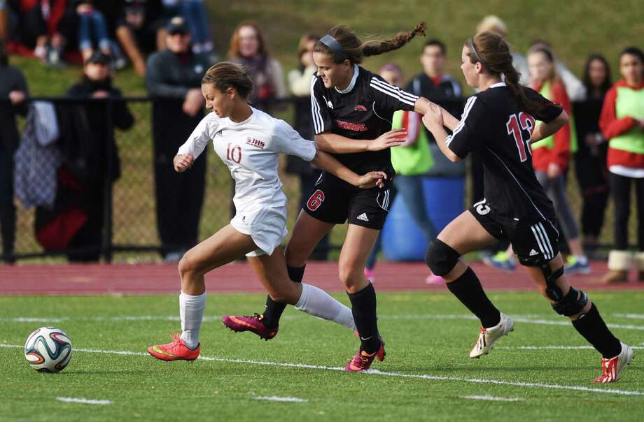 St. Joseph's Jenna Bike (10) makes a break past Fairfield Warde defenders Virginie Larouche (6) and Nicole Ciccarelli (13) in Fairfield Warde's 3-2 win over St. Joseph in the Class LL high school girls soccer quarterfinal game at St. Joseph High School in Trumbull, Conn. Sunday, Nov. 9, 2014. Photo: Tyler Sizemore / Greenwich Time
